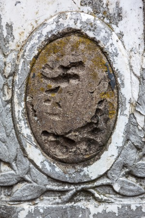 decedent: Old gravestone with damaged portrait of the buried person