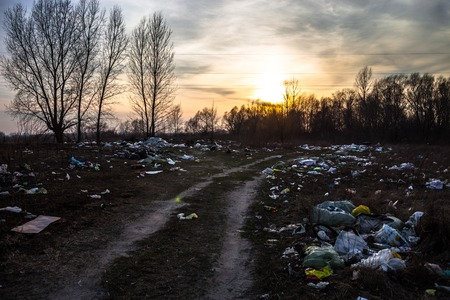 landfill site: Piles of garbage near the dirt road with sunset background
