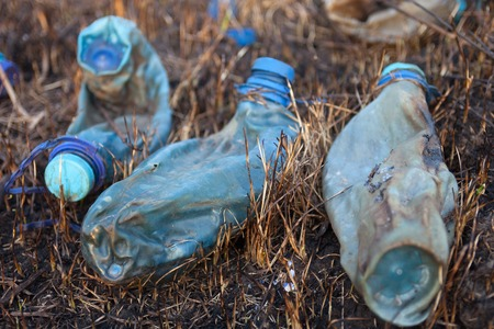Three melted plastic bottles on the burnt grass. photo