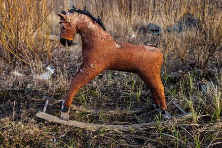 unneeded: Old threadbare rocking horse thrown away to the dump in the field