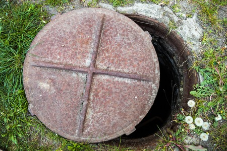 Open manhole with rusty metal cover in the grass  photo