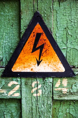 Old rusty warning high voltage sign on cracked green wooden surface photo