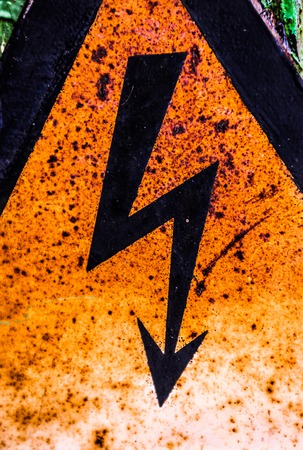 Close up of the old rusty warning high voltage sign photo