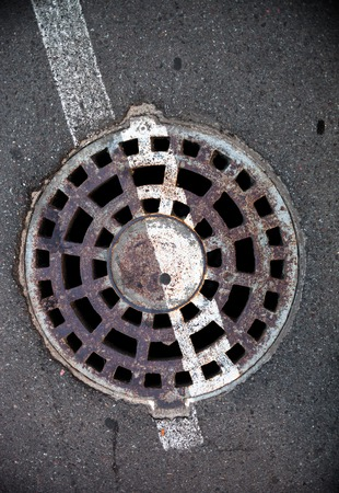 Manhole with metal cover in asphalt with white road marking line on it. photo