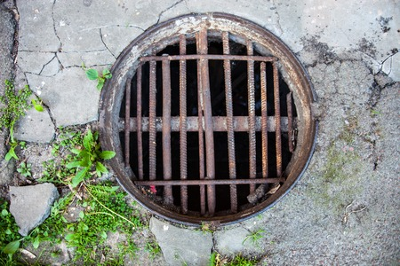 armature: Manhole with the handmade metal armature cover in the cracked concrete and asphalt surface