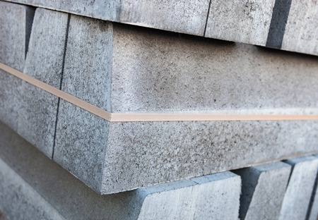 kerb: Stack of new concrete blocks tied-up with plastic stripe.