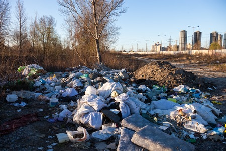 Garbage on the landfill near high-rise buildings of the city Stock Photo