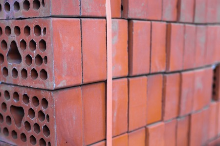 tiedup: Stack of new silicate bricks tied-up with plastic stripe. Close-up.