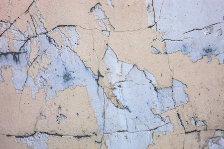 spattered: Cracked concrete surface with the remains of sandy-tan paint