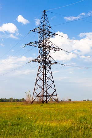 Electricity pylon on the green grass in the field against the cloudy sky background. photo