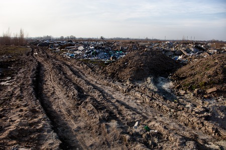 Piles of garbage on the city landfill near the dirt road photo