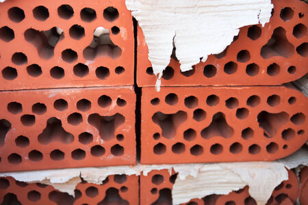rounded edges: Stack of silicate bricks with rounded edges and corrugated paper between the bricks. Closeup. Stock Photo