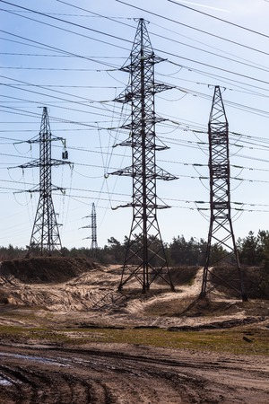 System of electricity pylons and power lines out-of-town near the dirt road, photo