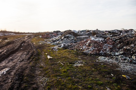 Piles of garbage on the city landfill near the dirt road
