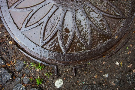 Closeup of the manhole with metal cover wet after the rain. photo