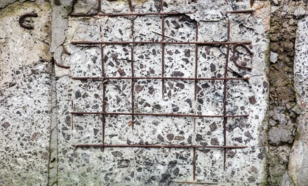 spattered: Grey concrete surface with visible blocks joints and reinforcement bars. Stock Photo