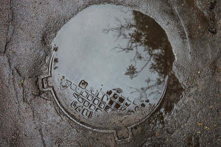 The puddle on the metal manhole in asphalt surface photo