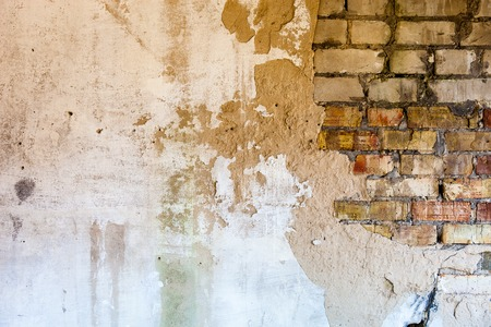 Old brick wall with the damaged plaster. photo