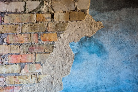 Old brick wall with the damaged blue-painted plaster. photo