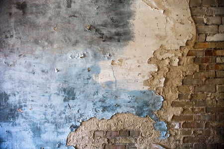 Damaged blue and white painted plaster on the old brick wall photo