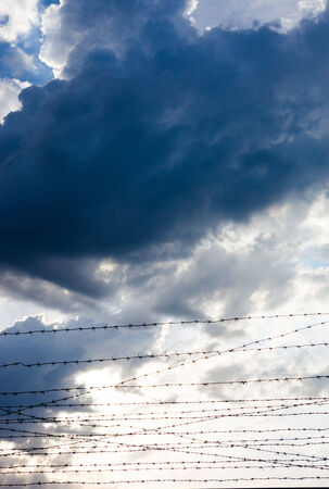 tenon: Barbed wires against the cloudy sky background. Stock Photo