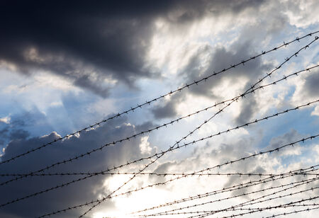 Barbed wire against the cloudy sky background. photo