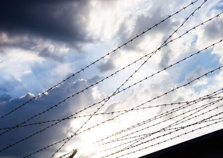 tenon: Barbed wire against the cloudy sky background.