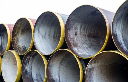 Stack of new metal pipes with yellow-painted edges. photo
