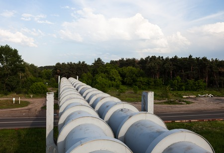 lagging: Elevated section of the pipelines above the road Stock Photo