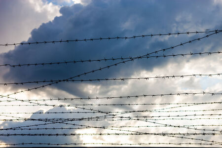 enclosing: Barbed wire against the cloudy sky background.