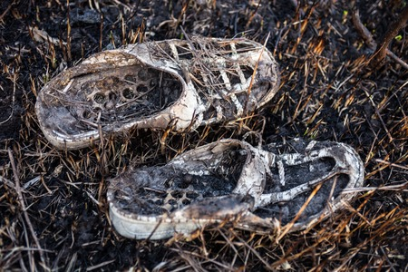 burnt: Old burnt shoes on the burnt grass.