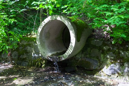 pollution: The concrete circular run-off pipe discharging water