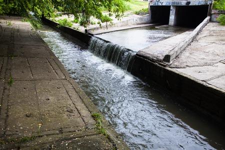 La corriente de agua que fluye hacia fuera del túnel subterráneo en el río Lybid en Kiev. Foto de archivo