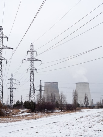 cooling towers: Electricity pylons, power lines and cooling towers of the cogeneration plant near Kyiv (Ukraine) in winter. Stock Photo