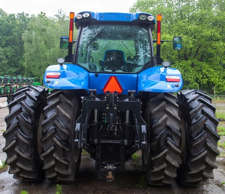 Rear view of the new blue tractor with huge rear wheels.