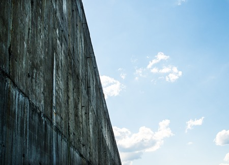 plaster mould: Gray concrete wall against the blue sky with white clouds.