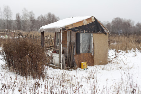 Temporary self-made shelter covered with the snow in winter. photo