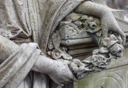 decedent: Womans hands holding the wreath. Old cemetery marble sculpture detail. Stock Photo