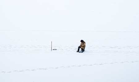 natural ice pastime: Fisherman sitting near the ice-hole on the frozen water surface covered with snow. Editorial