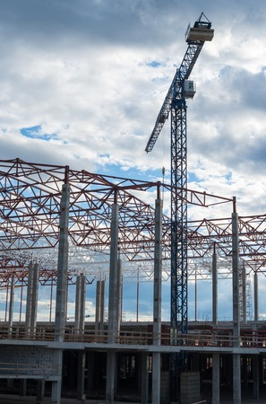 modern residential construction: Construction site. Framework of the new building and tower crane above it. Stock Photo