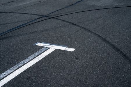 Asphalt surface of the empty parking with white road marking lines and wheel tracks photo
