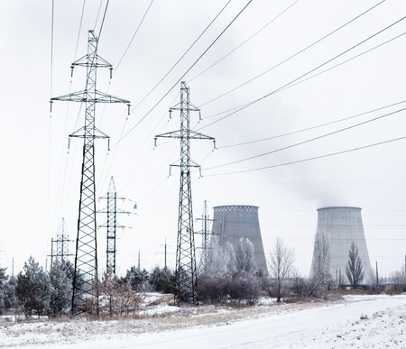 electric power station: Electricity pylons, power lines and cooling towers of the cogeneration plant near Kyiv (Ukraine) in winter. Stock Photo