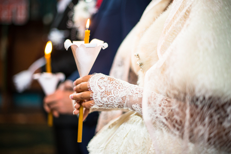 wedlock: Wedding ceremony in orthodox church. Bride and groom holding the candles. Close up. Stock Photo