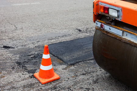 construction work: Road roller and traffic cone on the road construction. Stock Photo