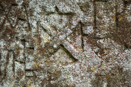 rood: Moss-grown surface of the old stone cross with engraved Old Church Slavonic inscriptions. Kyiv, Ukraine. Close up.