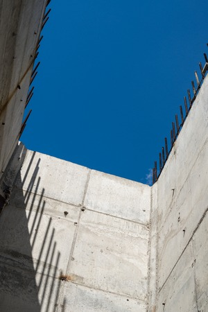 Grey concrete walls with reinforcing bars against the blue sky background photo