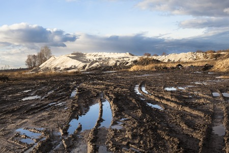 Mud and puddles on the dirt road with sand hills in the background. Standard-Bild