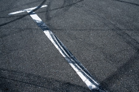 Asphalt surface of the empty parking with white road marking lines and wheel tracks