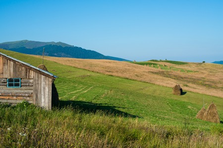 Summer landscape in the Ukrainian Carpathian Mountains with the wooden shed in the foreground, photo