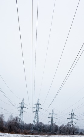 System of electricity pylons and power lines out-of-town in the winter day. photo